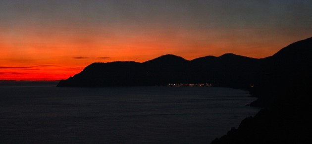 Sunset over the hills with lights of Vernazza and Monterosso